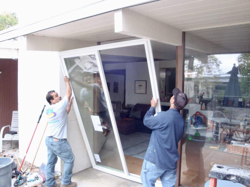 Save Energy workers install a sliding glass door in a San Francisco home.