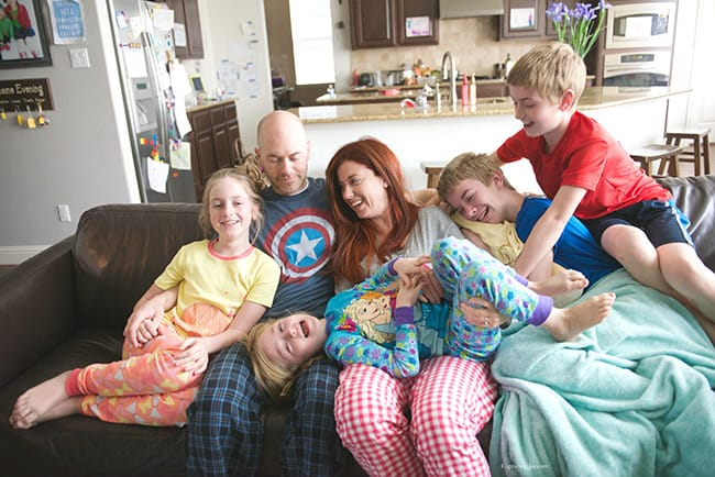 A husband and wife cuddle with their family of children on the couch.